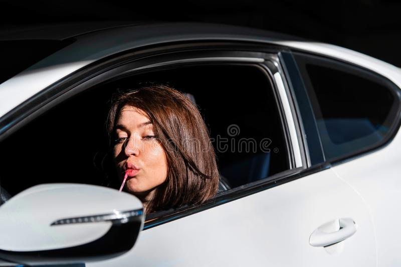 Confident and beautiful young business woman painting her lips in new car and looking into Side view mirror stock image