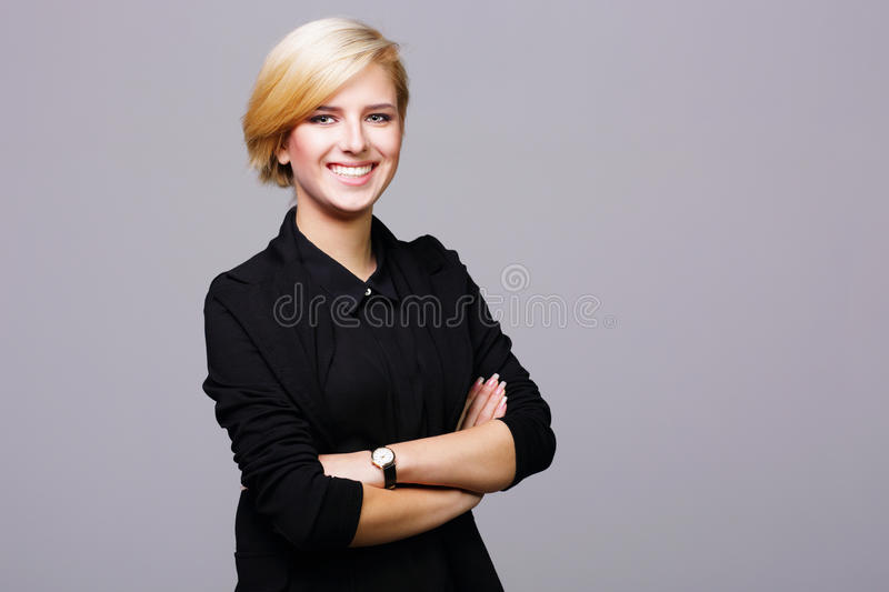 Confident beautiful young woman with arms folded. On gray background royalty free stock images