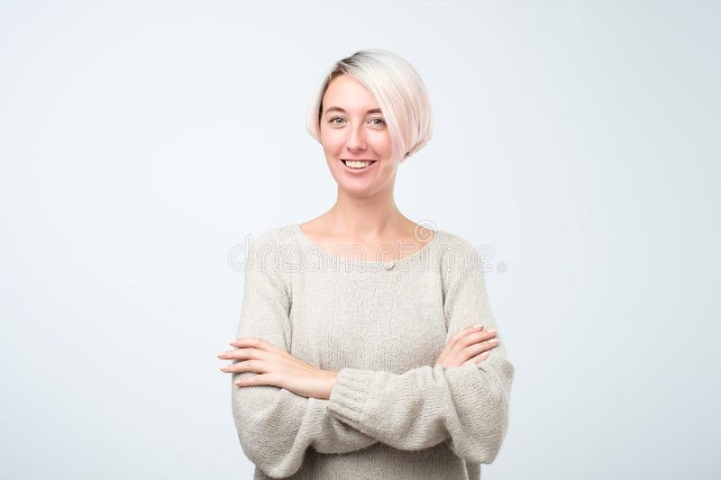 Confident and beautiful young woman looking at camera and smiling while standing against grey background stock photos