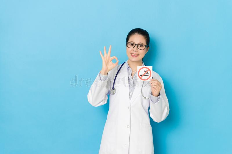 Confident beauty doctor woman showing ok gesture. With quit smoking and standing in blue background looking at camera smiling royalty free stock photography