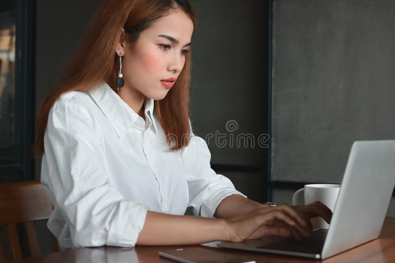 Confident beauty young Asian business woman working with laptop in workplace of office. royalty free stock photography