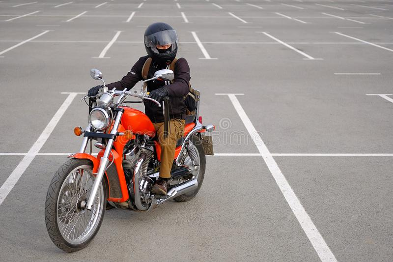 Confident biker a man or a guy-racer in a protective helmet sits on a classic-style motorcycle, looking away, in the Parking lot royalty free stock photography