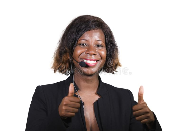 Confident black African American business woman with headset speaking at corporate seminar event in motivation coaching conference. Young attractive and royalty free stock image