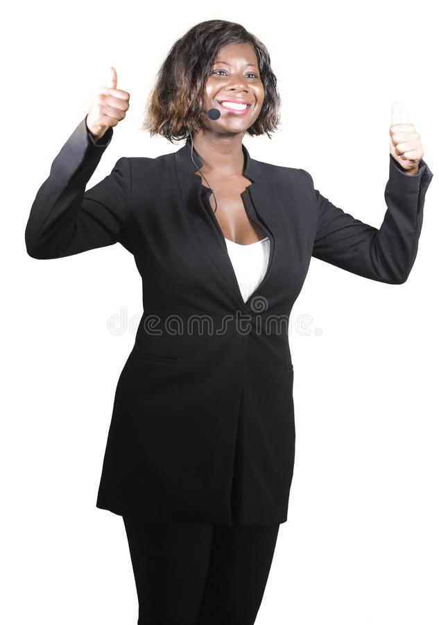 Confident black African American business woman with headset speaking at corporate seminar event in motivation coaching conference. Young attractive and stock photo