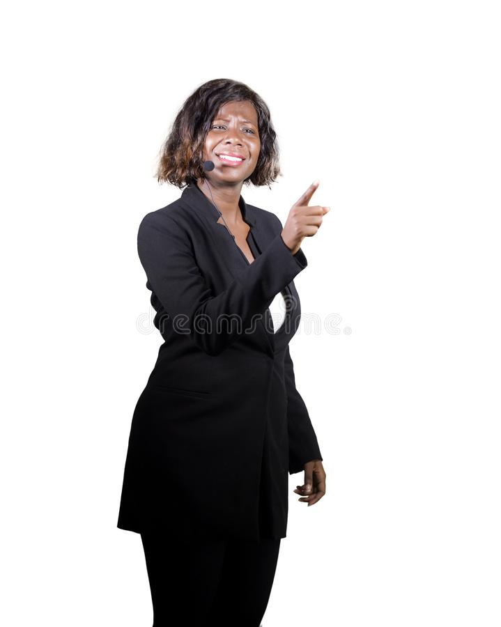 Confident black African American business woman with headset speaking at corporate seminar event in motivation coaching conference. Young attractive and royalty free stock photography