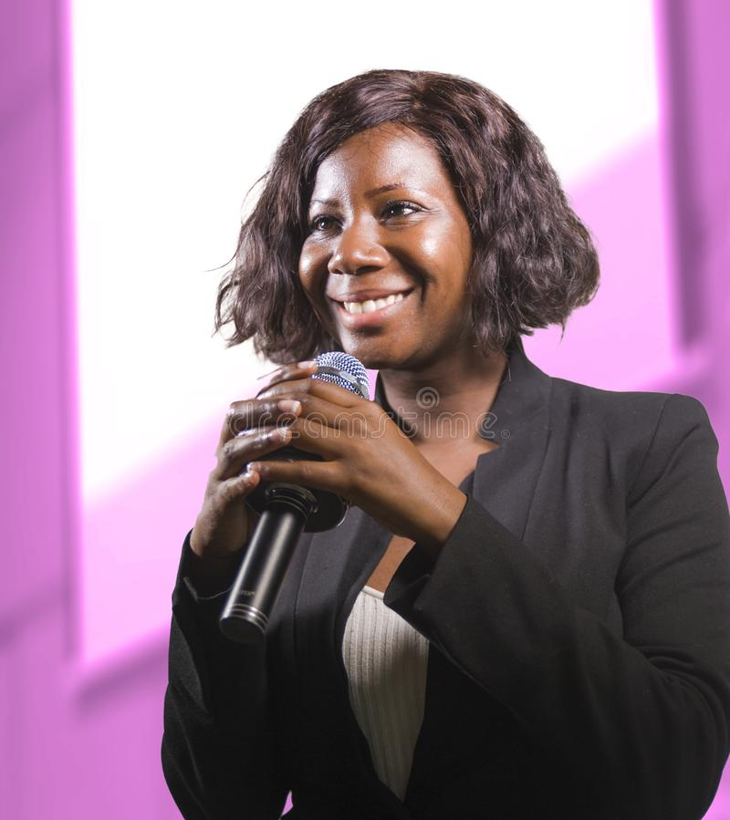 Confident black African American business woman with microphone speaking in auditorium at corporate event or seminar giving royalty free stock photos