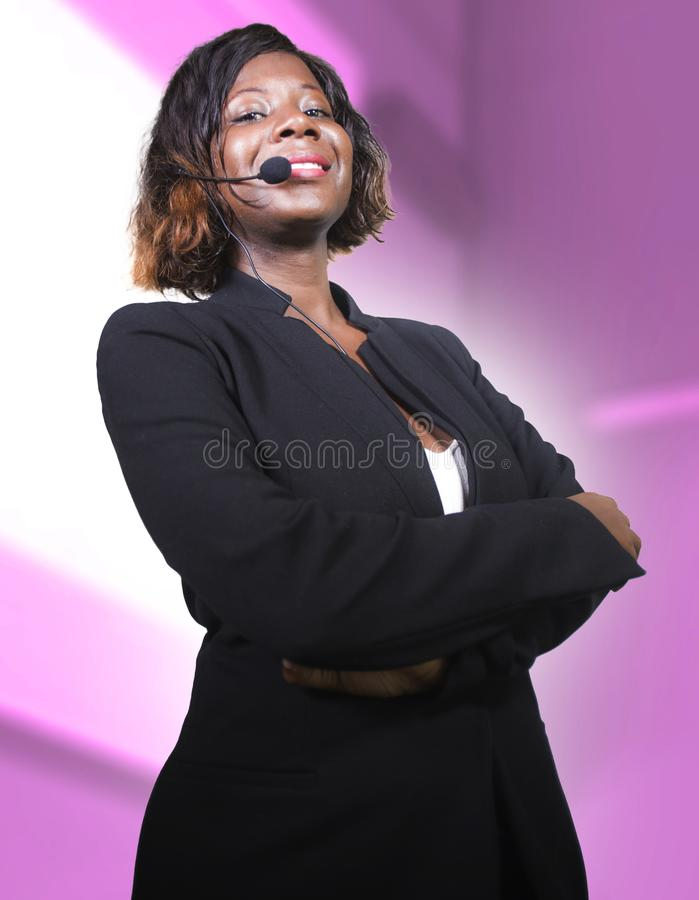 Confident black African American business woman with microphone speaking in auditorium at corporate seminar event giving success. Young attractive and confident royalty free stock image