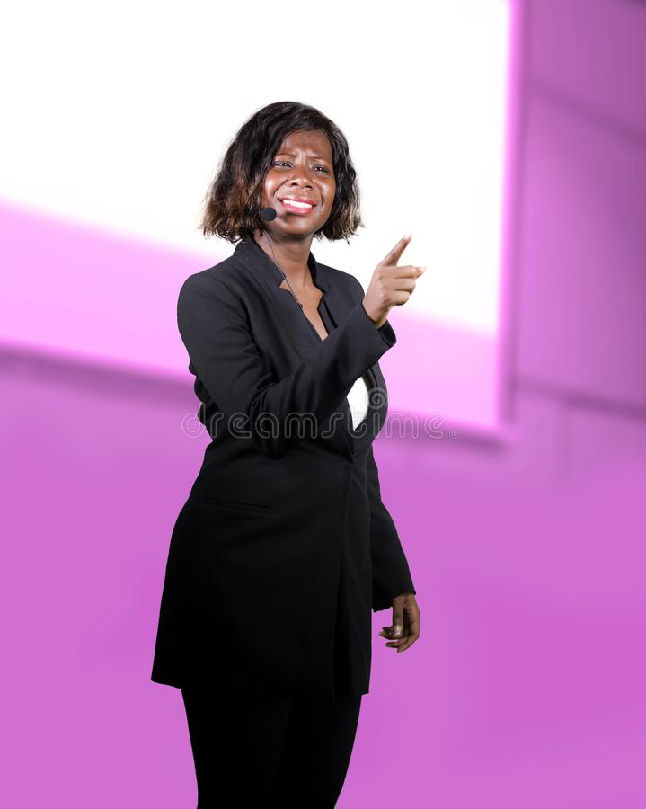 Confident black African American business woman with microphone speaking in auditorium at corporate seminar event giving success. Young attractive and confident royalty free stock photos