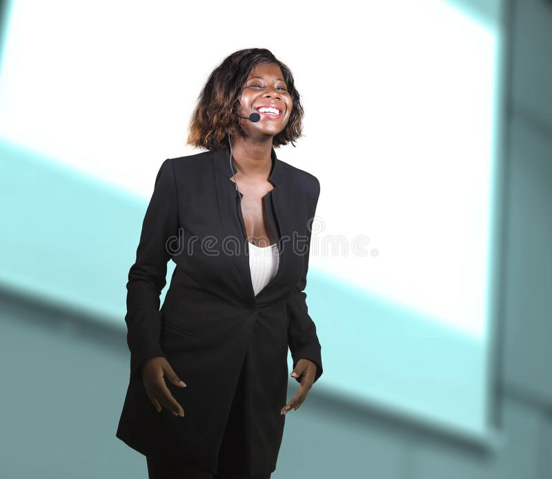 Confident black afro American business woman with microphone speaking in auditorium at corporate seminar event giving success. Young attractive and confident royalty free stock images