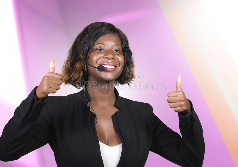 Confident black afro American business woman with microphone speaking in auditorium at corporate seminar event giving success. Young attractive and confident stock images