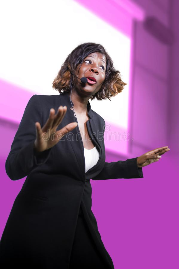Confident black afro American business woman with microphone speaking in auditorium at corporate seminar event giving success. Young attractive and confident stock photos