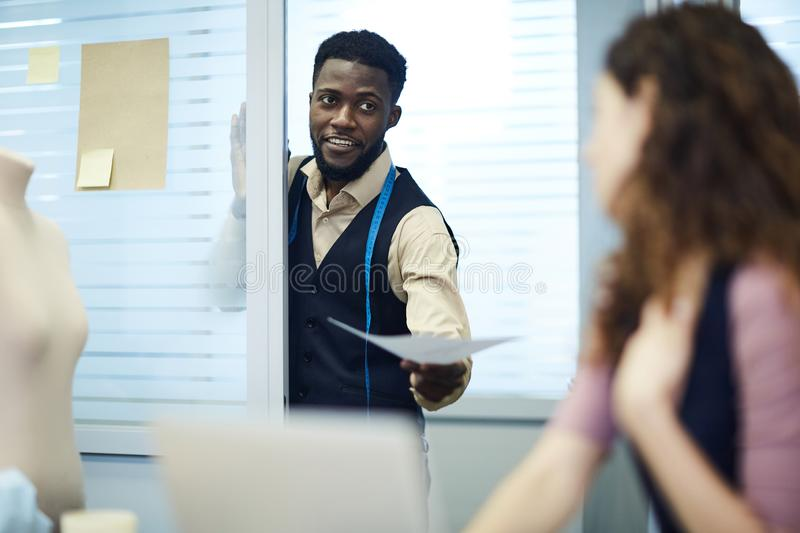 Confident black assistant giving sketch to lady dressmaker royalty free stock image