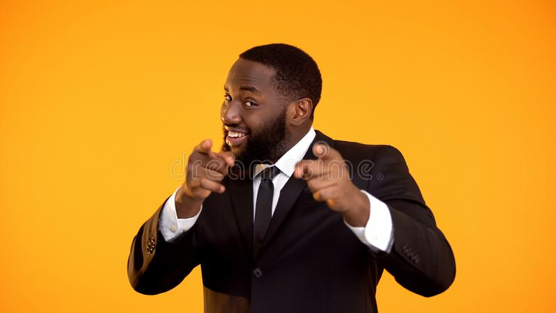 Confident black businessman pointing fingers, making choose you movement, promo stock photos
