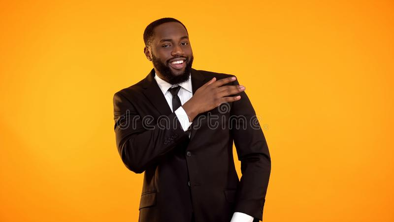 Confident black businessman shaking dust of formal suit, dry cleaning services stock photography