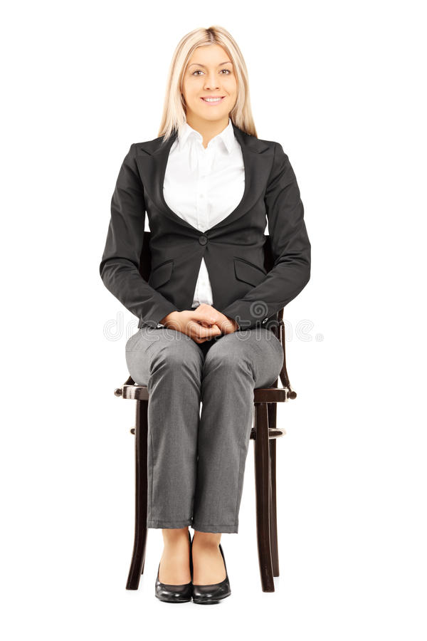 Confident blond businesswoman in suit sitting on a chair. Confident blond businesswoman in suit sitting on a wooden chair isolated on white background royalty free stock image