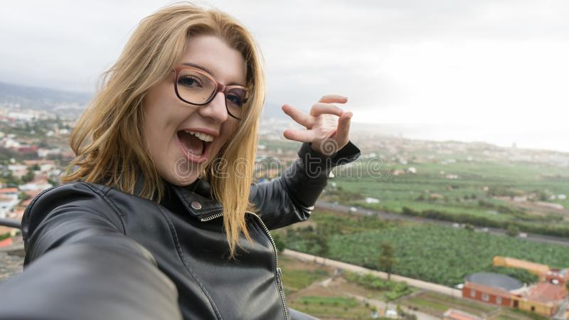 Confident Blond Lady taking a picture with her camera in a viewpoint. Teenager in glasses with short hair smiling showing teeth stock photography