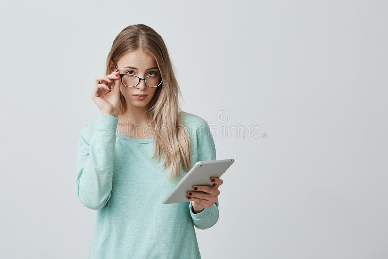Confident blonde female enterpreneur in stylish eyewear stands with tablet against gray wall, works on developing new royalty free stock images