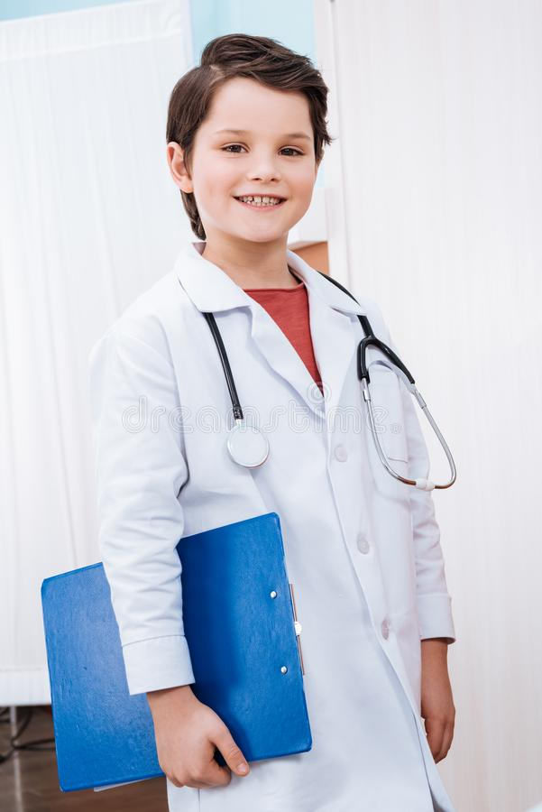 Confident boy doctor with stethoscope holding folder and smiling royalty free stock images