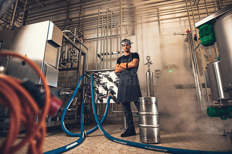 Confident brewer in apron at brewery factory. Confident brewer in apron with arms crossed looking at camera while standing in front of industrial equipments at royalty free stock photography