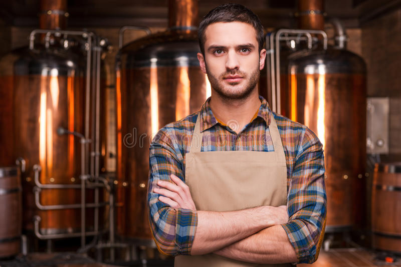Confident brewer. Confident young male brewer in apron keeping arms crossed and looking at camera while standing in front of metal containers royalty free stock image