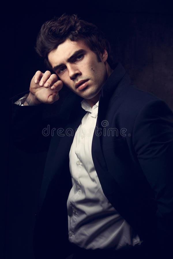 Confident brutal man with strained look posing in blue fashion s. Uit and white style shirt on dark shadow background. Closeup portrait royalty free stock photography