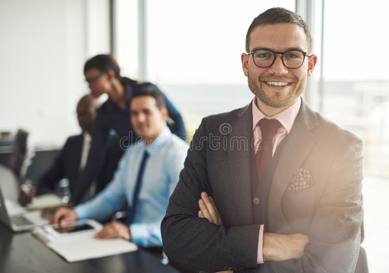 Confident business executive with folded arms. Confident smiling business executive with folded arms near conference table with three co-workers discussing stock photography