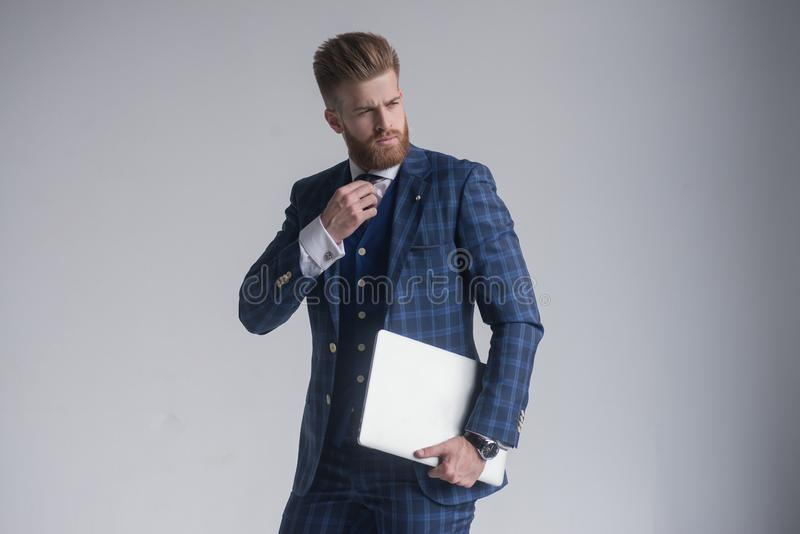 Confident business expert. Confident young handsome man in three piece suit holding laptop and smiling while standing against stock photography