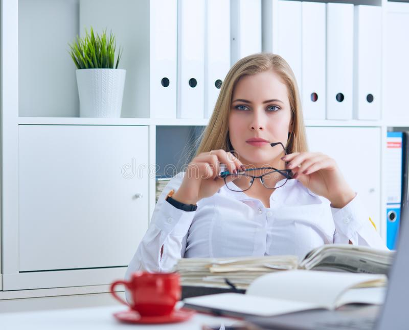 Confident business lady. Beautiful young woman in formalwear holding a paper and adjusting glasses while sitting at the stock image