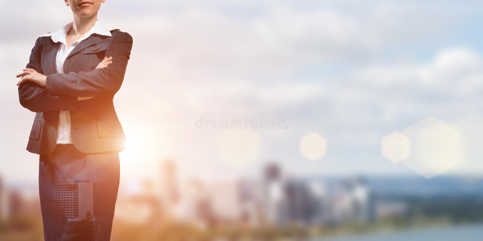 Confident business leader. Close up of businesswoman with arms crossed on chest on modern city background stock photo