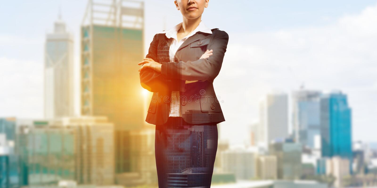 Confident business leader. Close up of businesswoman with arms crossed on chest on modern city background royalty free stock photo