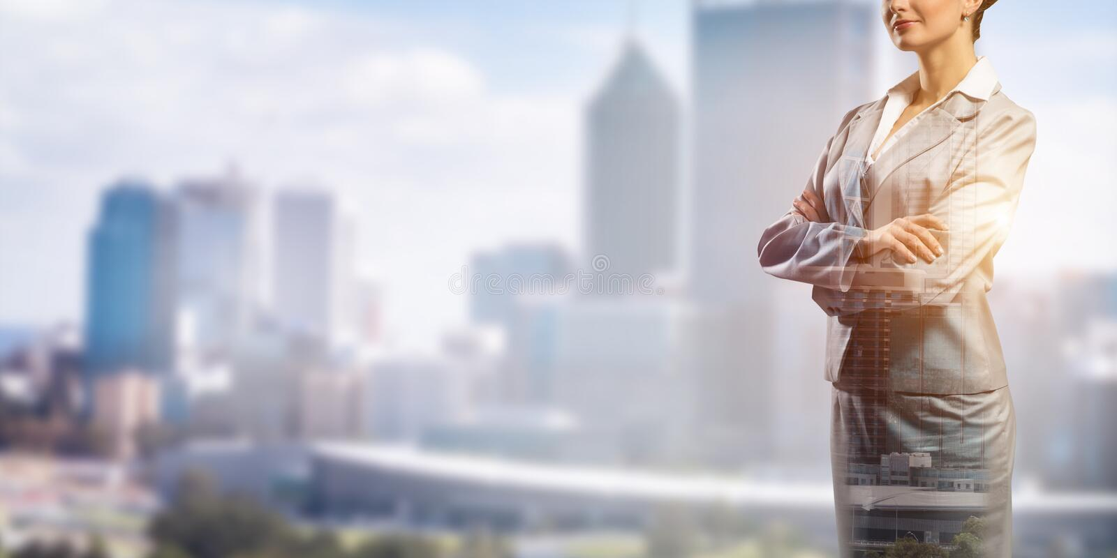 Confident business leader. Close up of businesswoman with arms crossed on chest on modern city background stock image