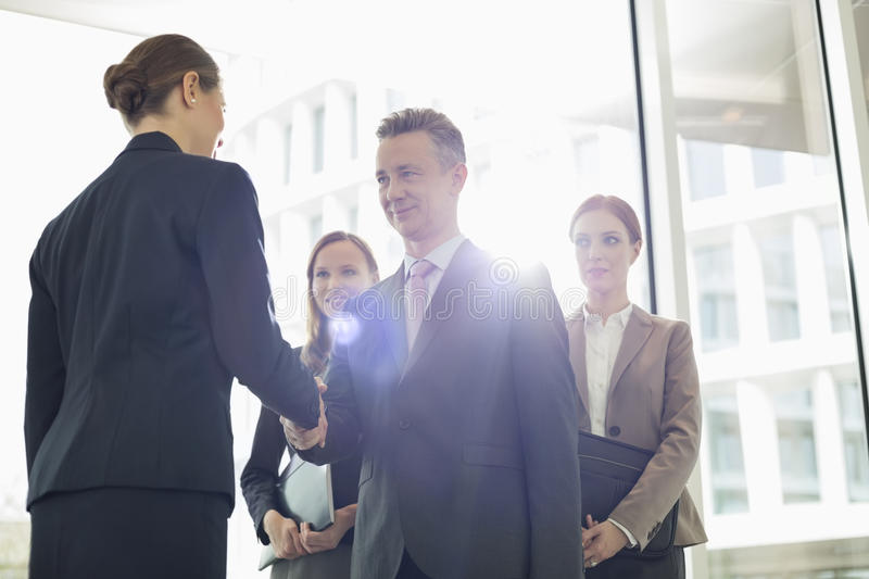 Confident business partners shaking hands in office royalty free stock images