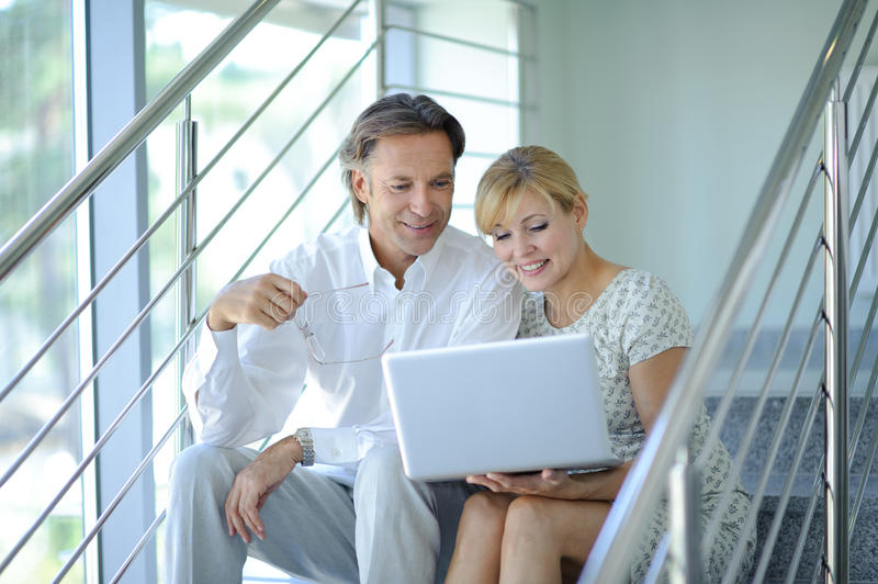 Confident business partners sitting on stairs in office building and discussing work, computer, smiling, mature businessman stock photos