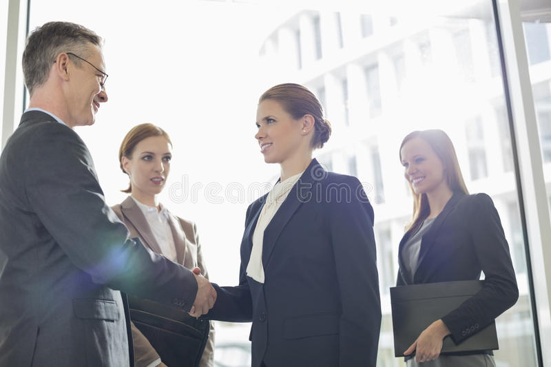 Confident business people shaking hands in office stock image