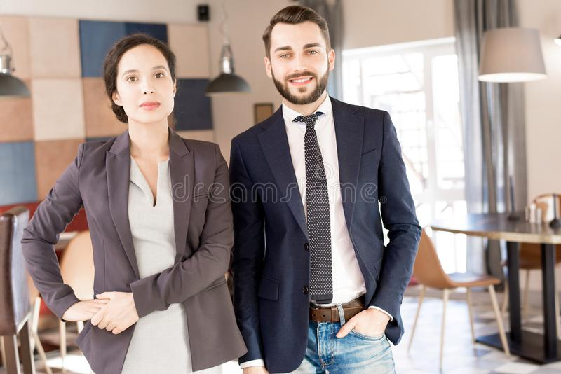 Confident business team in hall. Serious confident young multiethnic business team members in smart casual outfits standing in restaurant hall and looking at royalty free stock image