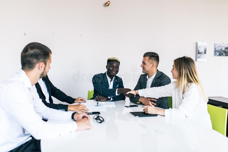 Confident business team of mixed ages and ethnicity making handshaking while meeting in a modern office. They are discussing ideas royalty free stock images