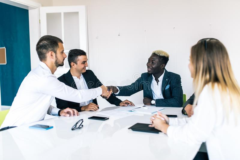Confident business team of mixed ages and ethnicity making handshaking while meeting in a modern office. They are discussing ideas stock images