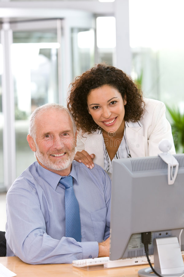 Confident business team working on computer stock photo