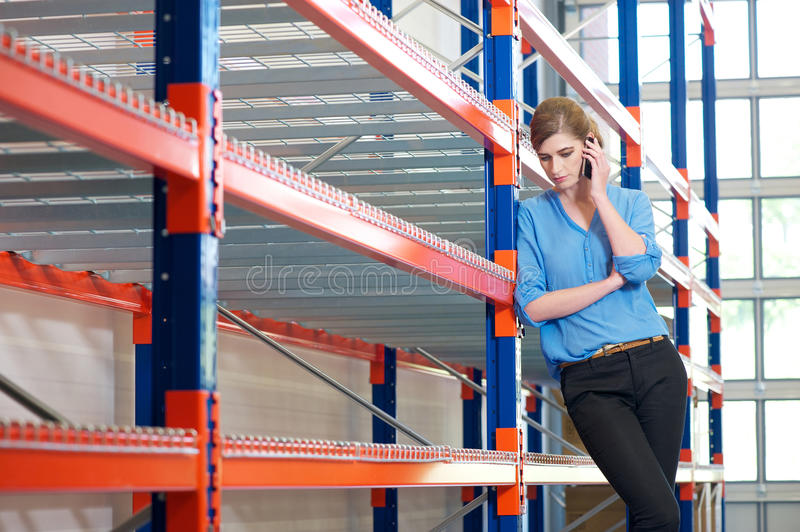 Download Confident Business Woman  On Cellphone In Warehouse Stock Image - Image: 31966119