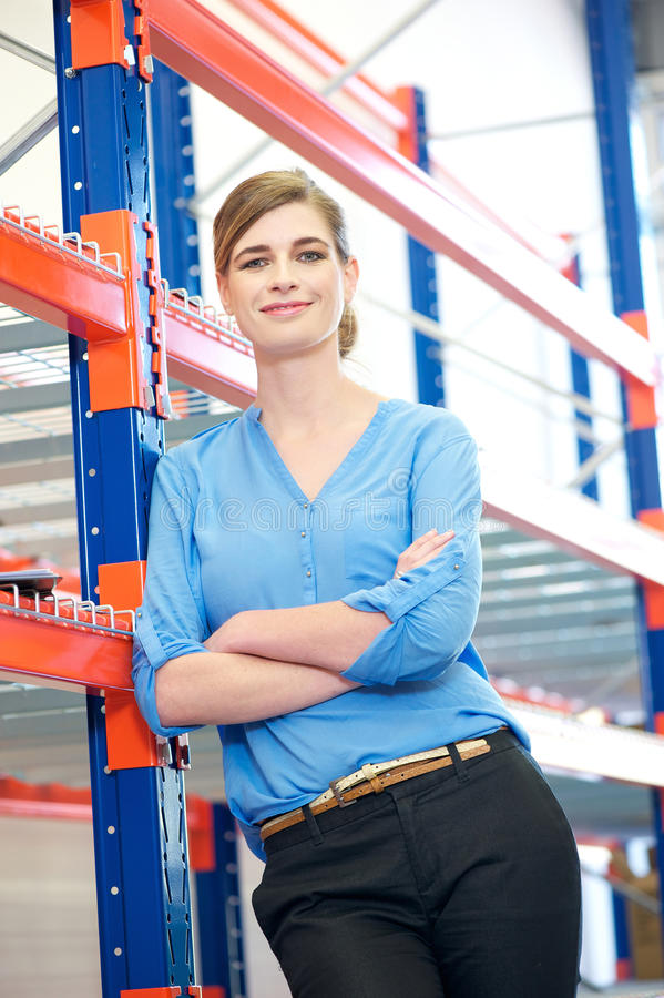 Confident business woman relaxing next to shelve racks in warehouse royalty free stock image