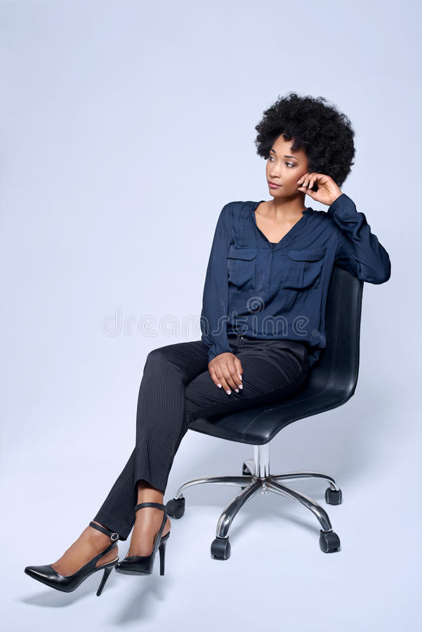 Confident business woman sitting in studio. Potrait of confident black african business woman sitting on executive chair in studio, isolated on grey background stock photos