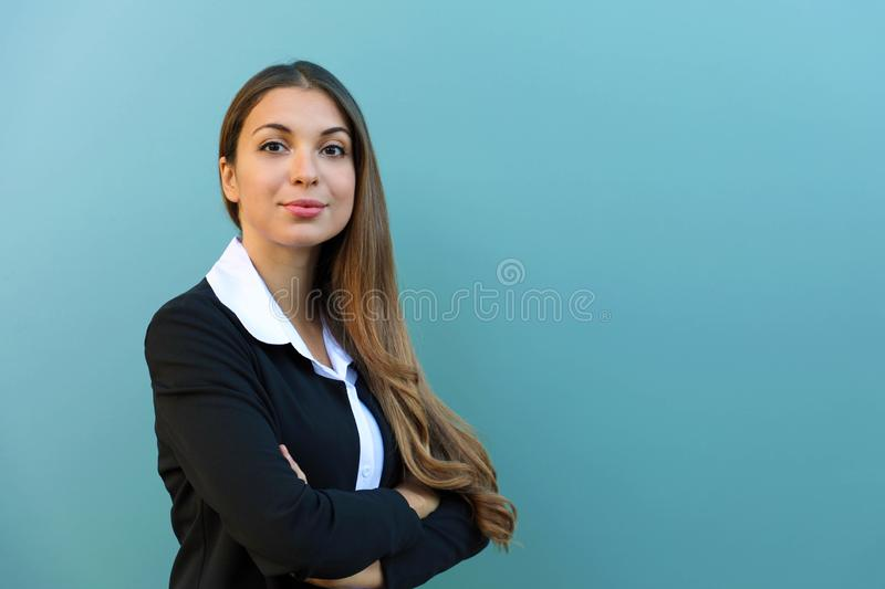 Confident business woman with suit standing against blue background with crossed arms outdoor. Copy space royalty free stock image