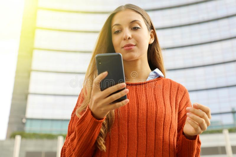 Confident business woman using smart phone with modern skyscraper on the background stock photo