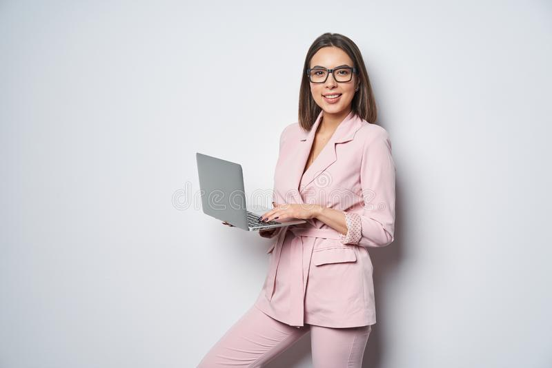 Confident business woman wearing pink suit holding opened laptop royalty free stock image