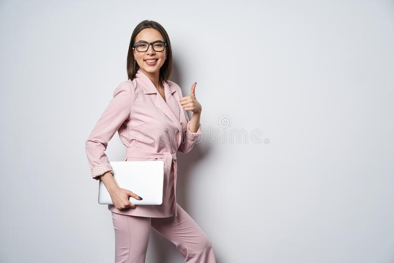 Confident business woman wearing pink suit with laptop underarm stock images