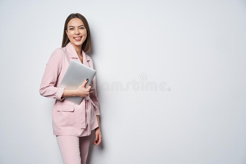 Confident business woman wearing pink suit with laptop underarm royalty free stock image