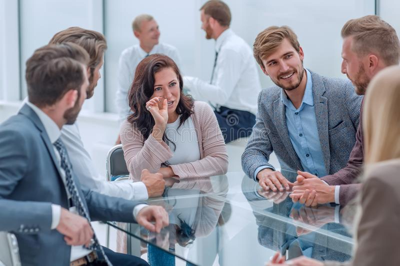 Confident business woman explaining something to her business partners stock photo