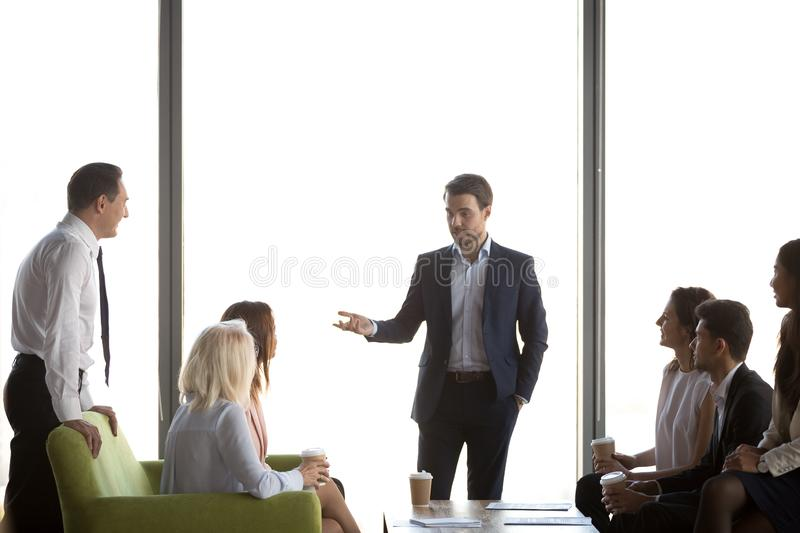 Confident businessman, coach holding business briefing with workers royalty free stock images
