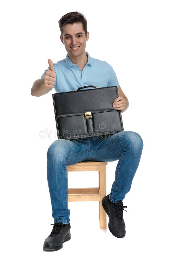Confident businessman giving a thumbs up and holding a briefcase stock photos