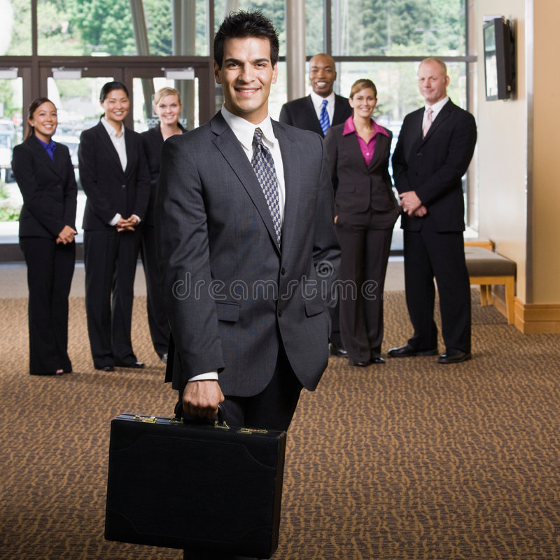 Confident businessman holding briefcase stock photo